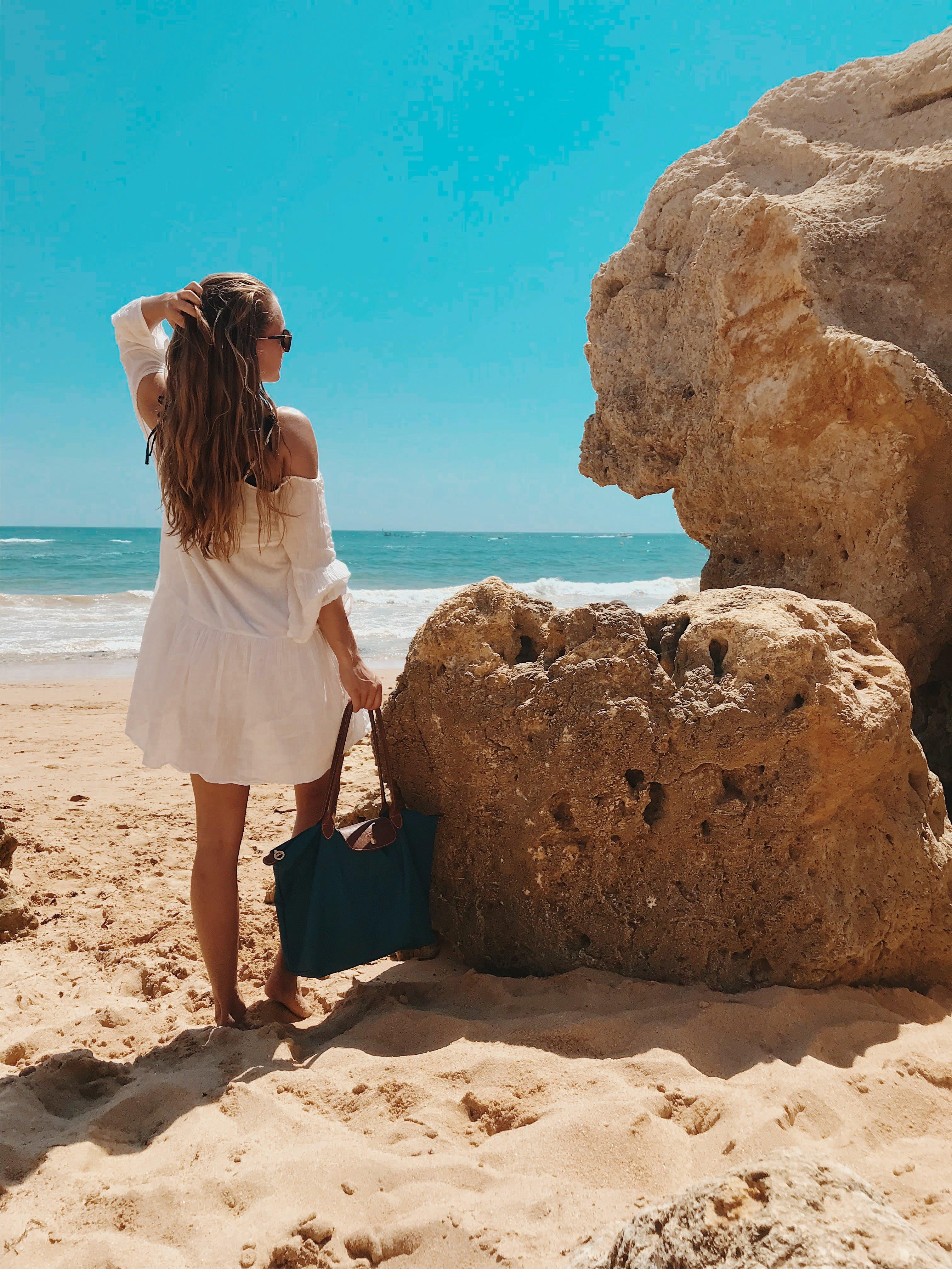 Woman Standing Beside Rocks Near Beach