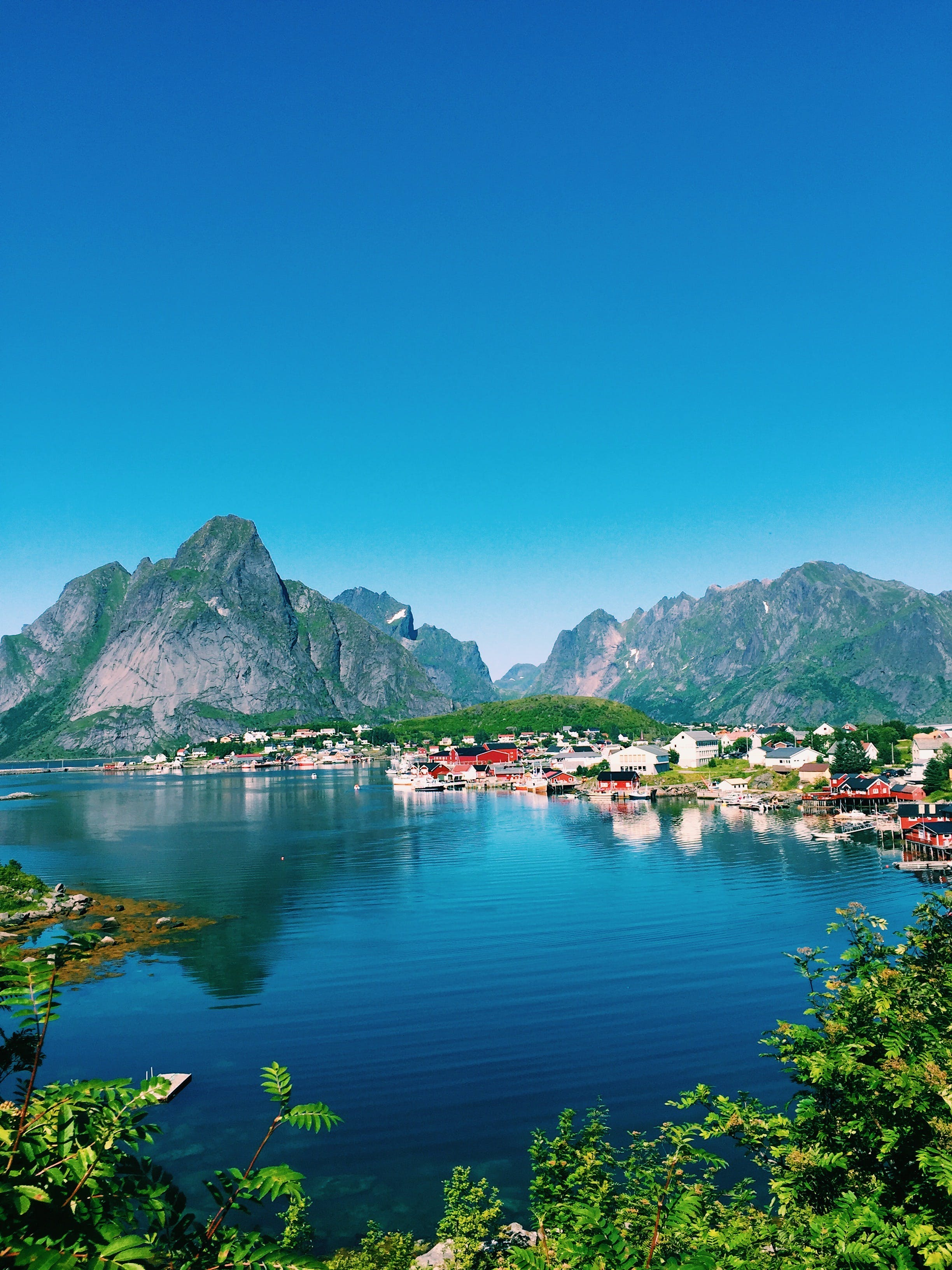 Large Body of Water Across Village and Mountains Under Blue Skies