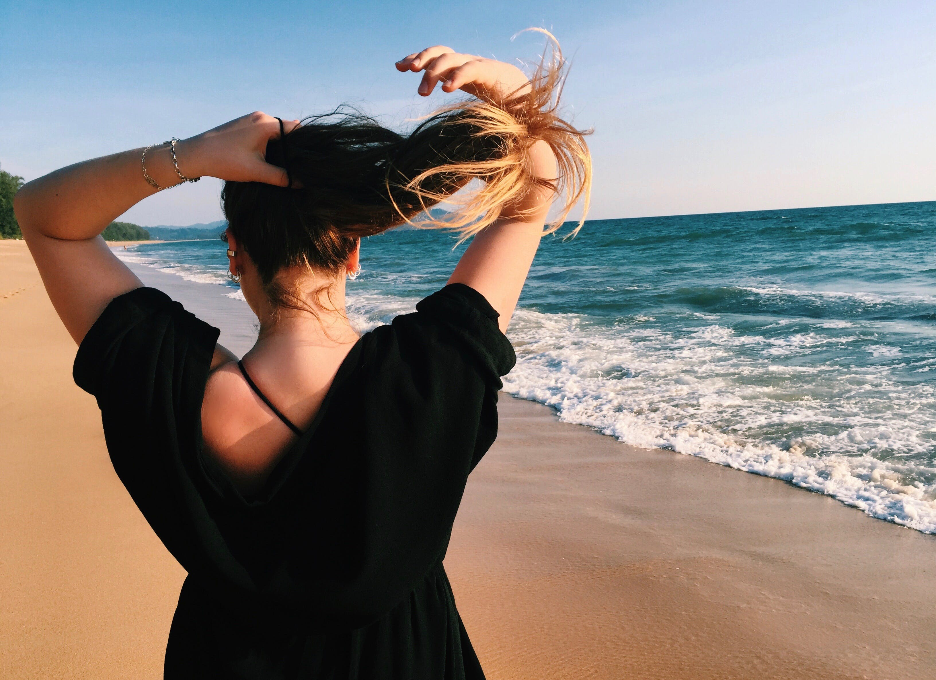 Woman Holding Her Hair While Standing Beside Shoreline
