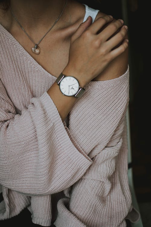Woman Wearing Beige Crochet Sweater and Round White Analog Watch Closeup Photo