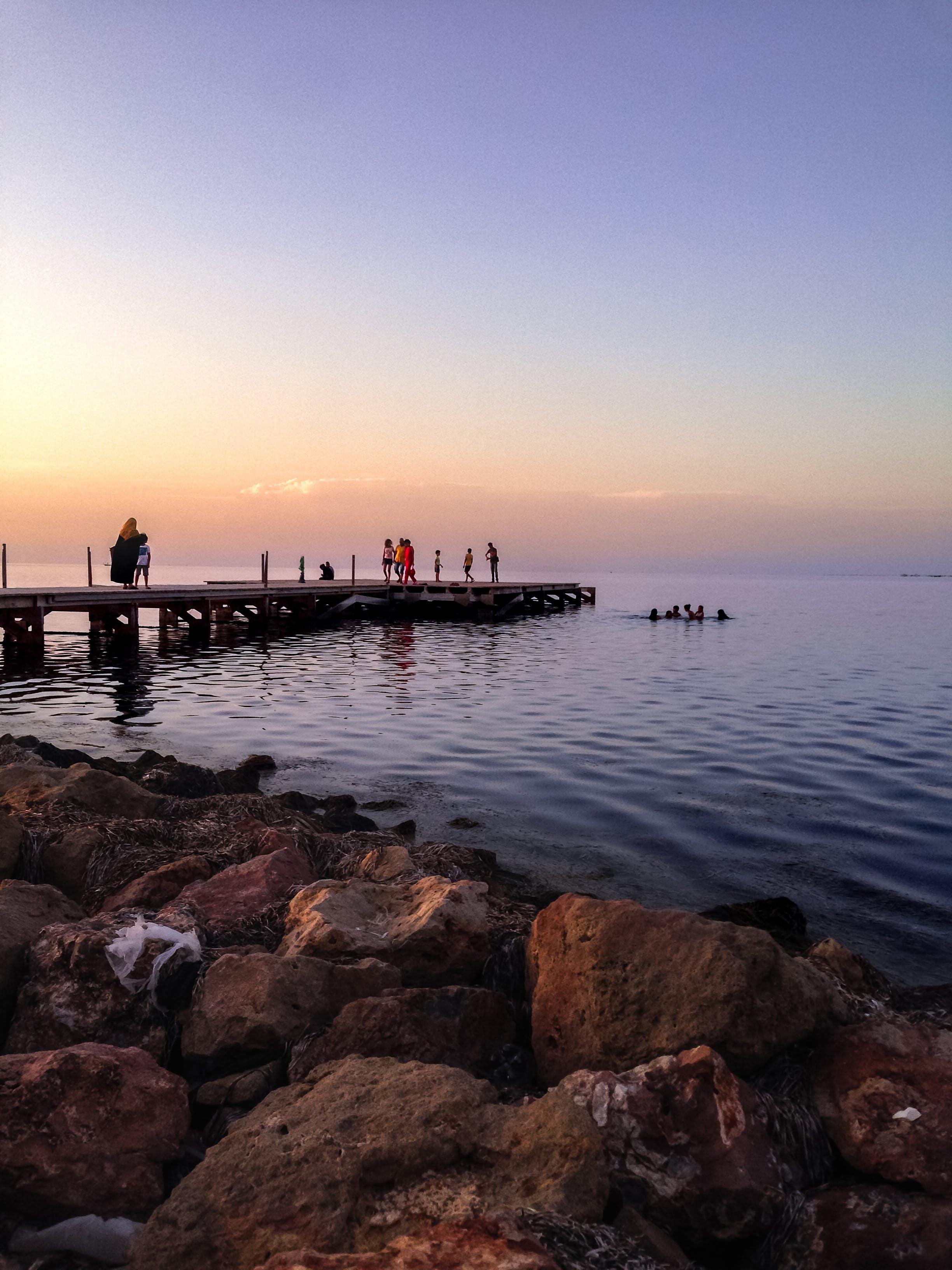 People Walking On Wooden Dock