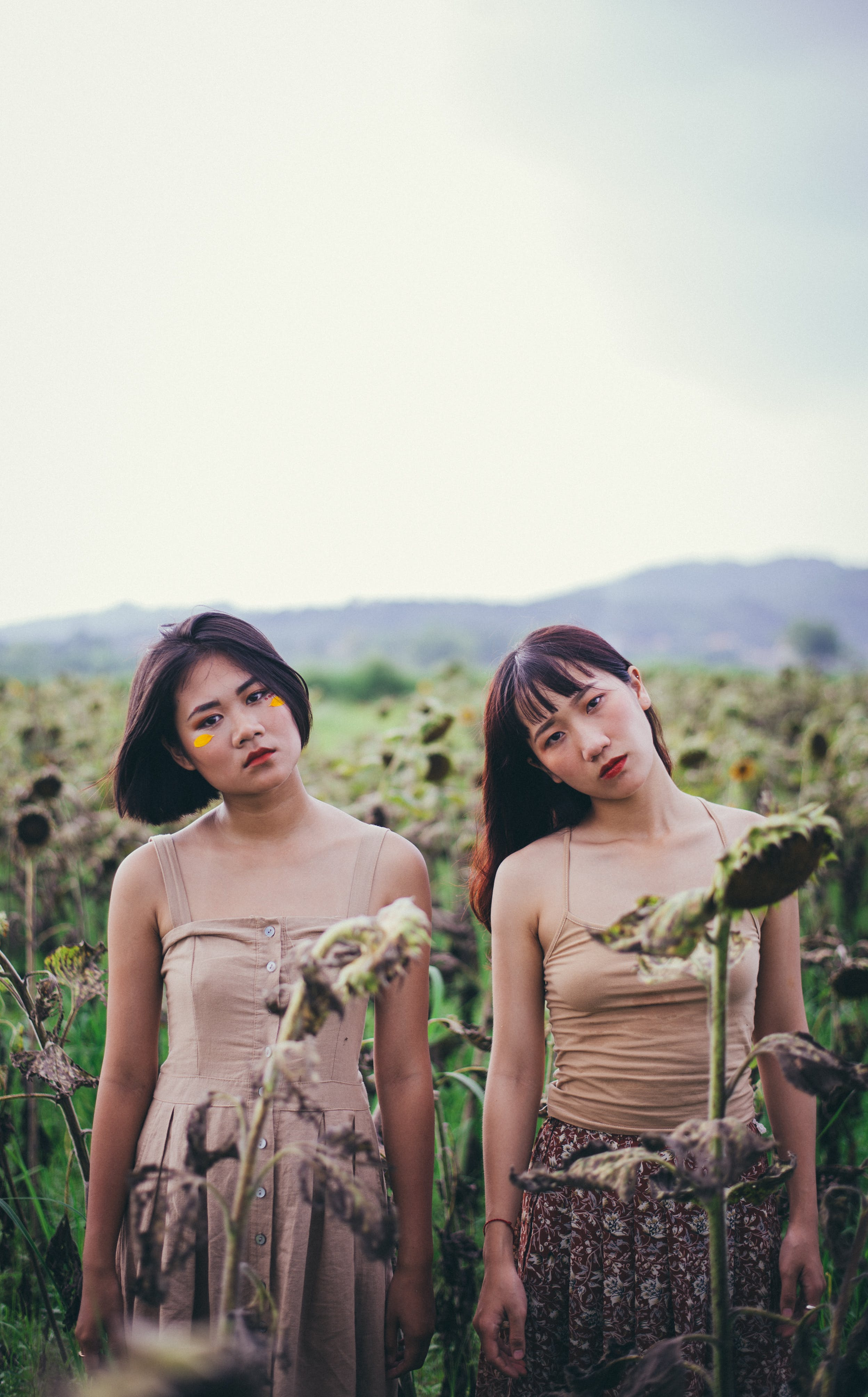 Close-up Photo of Two Women Standing on Sunflower Field