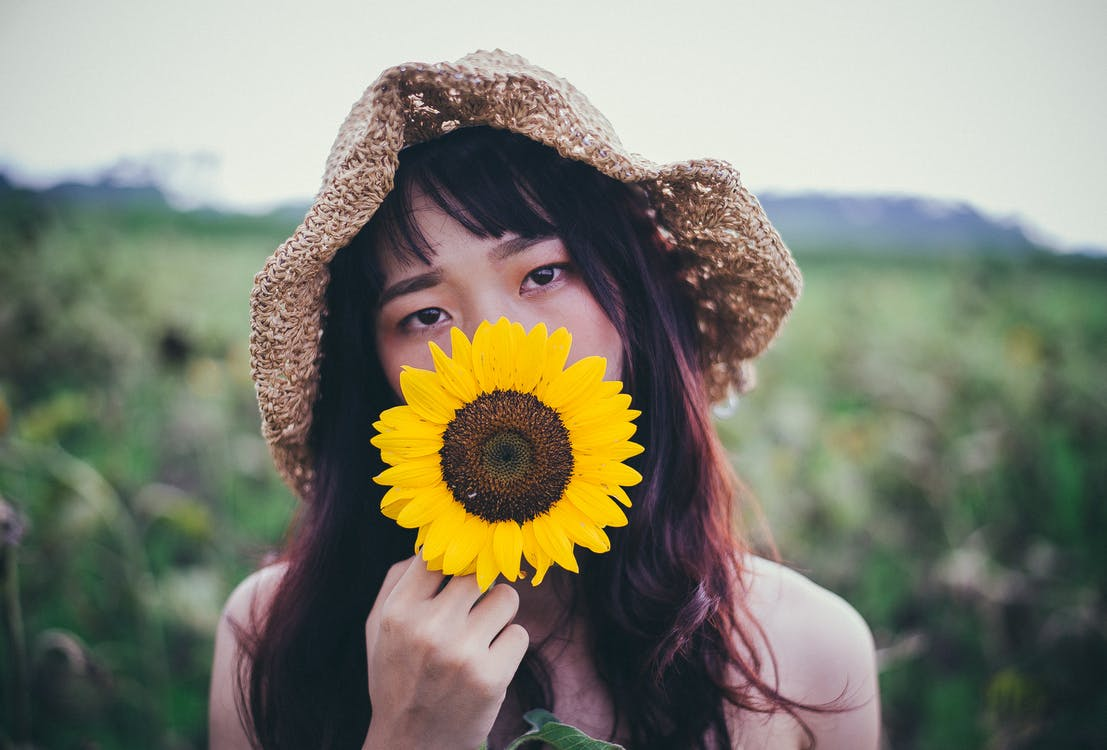 Woman in Brown Sun Hat Holding Sunflower