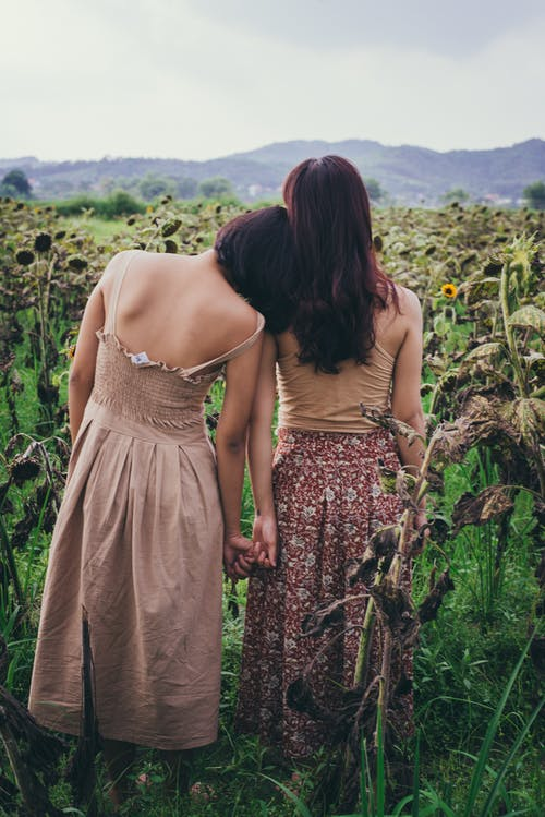 Two Women StandingIn Sunflower Field