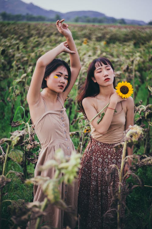 Two Woman Standing In The Middle Of Sunflower Field