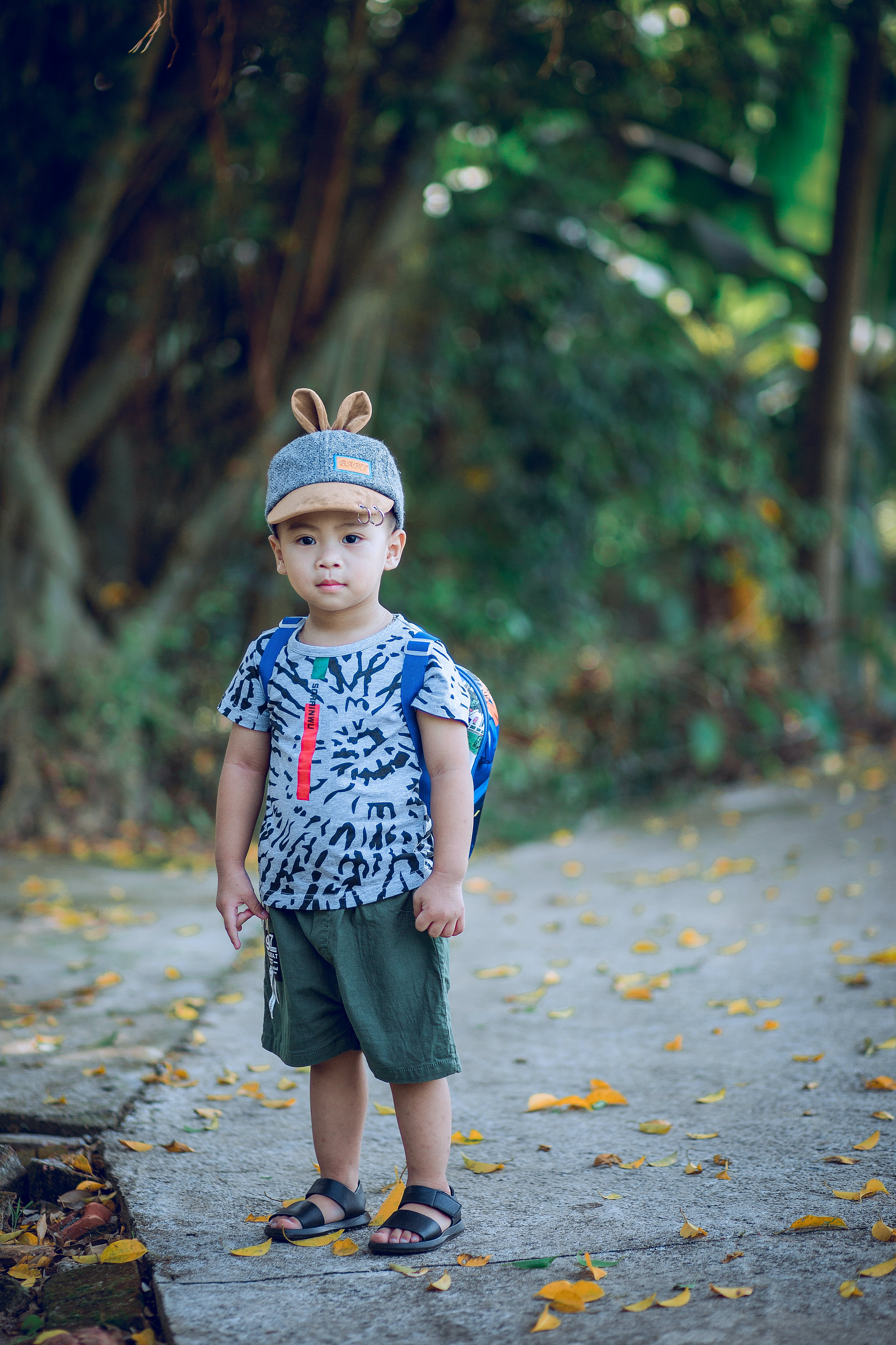 Boy Wearing Shirt and Backpack Standing on Concrete Pathway