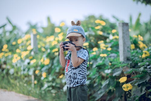 Boy Holding Camera In Front of Yellow Flowers