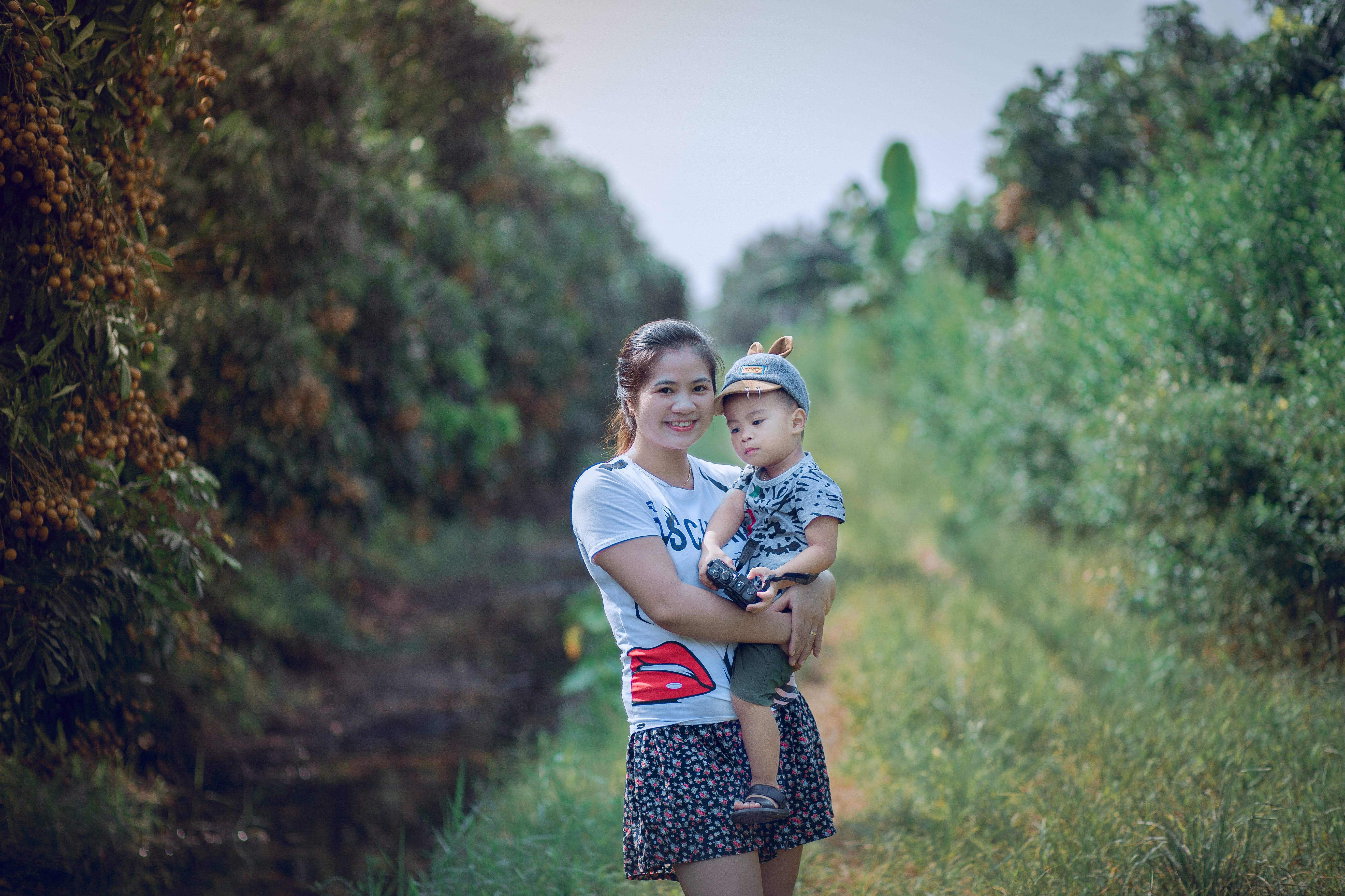 Woman Carrying Her Son Standing Between Trees