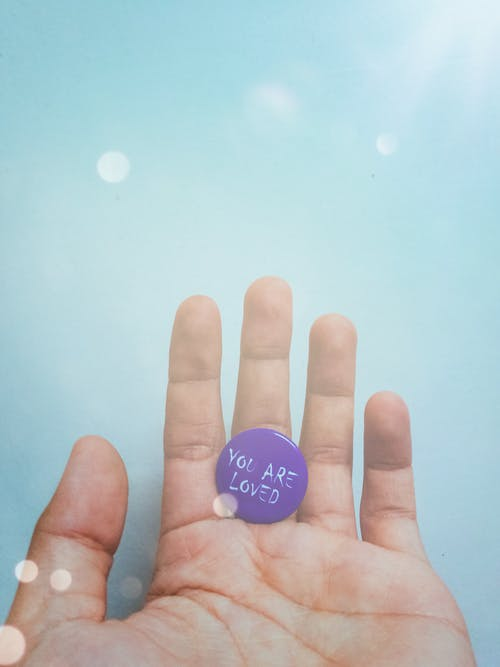Person Holding Purple Badge You Are Loved Text-printed