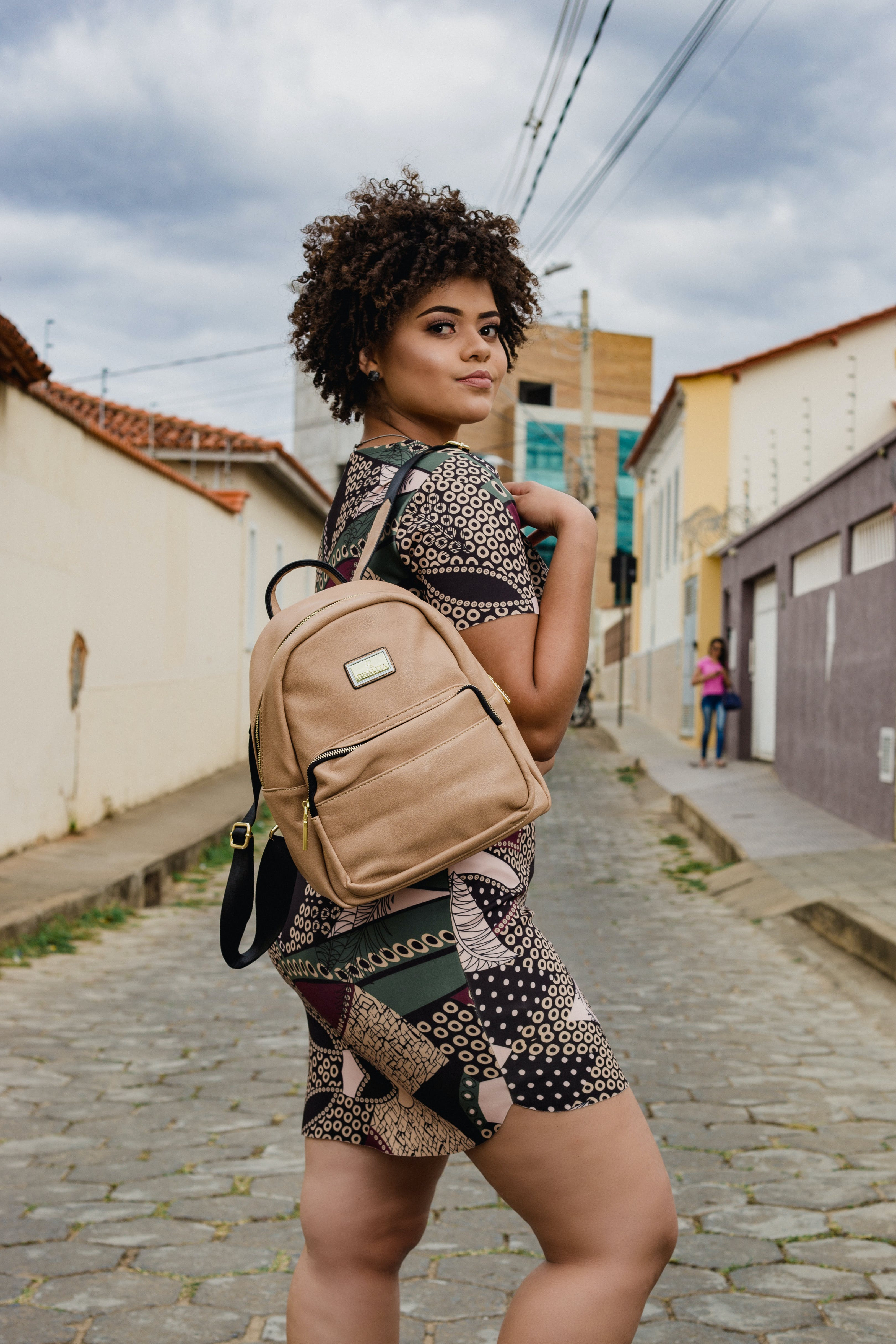 Woman in Black, Beige, and Green Dress With Brown Backpack