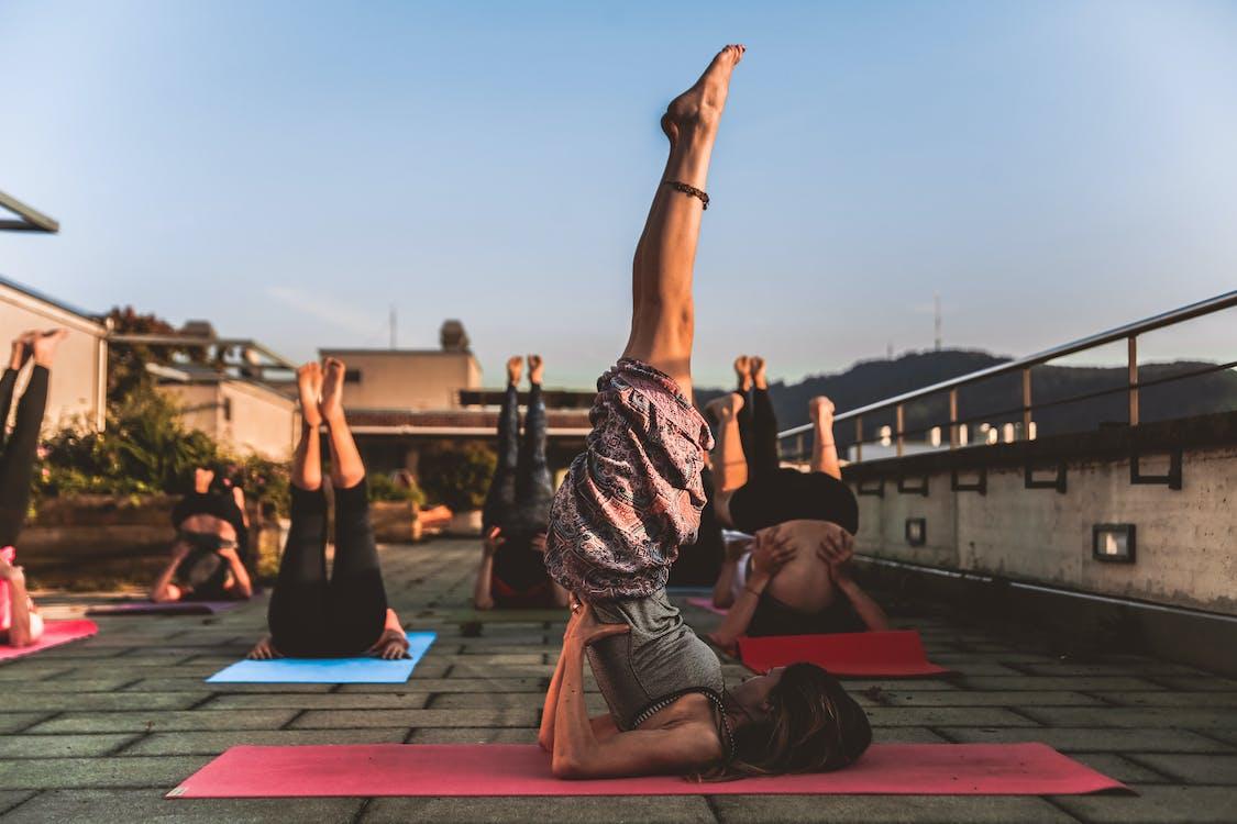Group of Women Lying on Yoga Mat Under Blue Sky