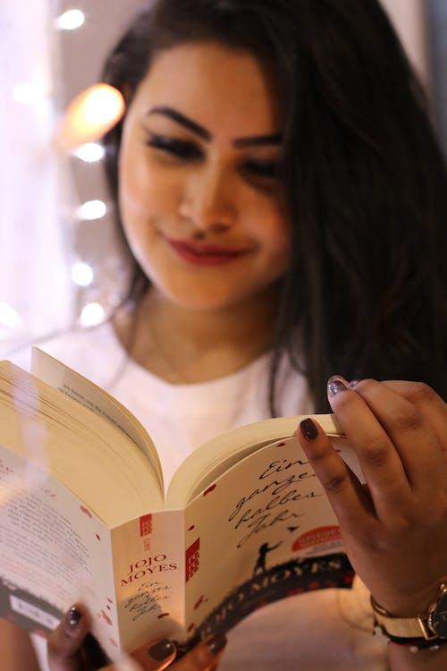 Woman Wearing White Crew-neck Shirt Holding Jojo Moyes Book