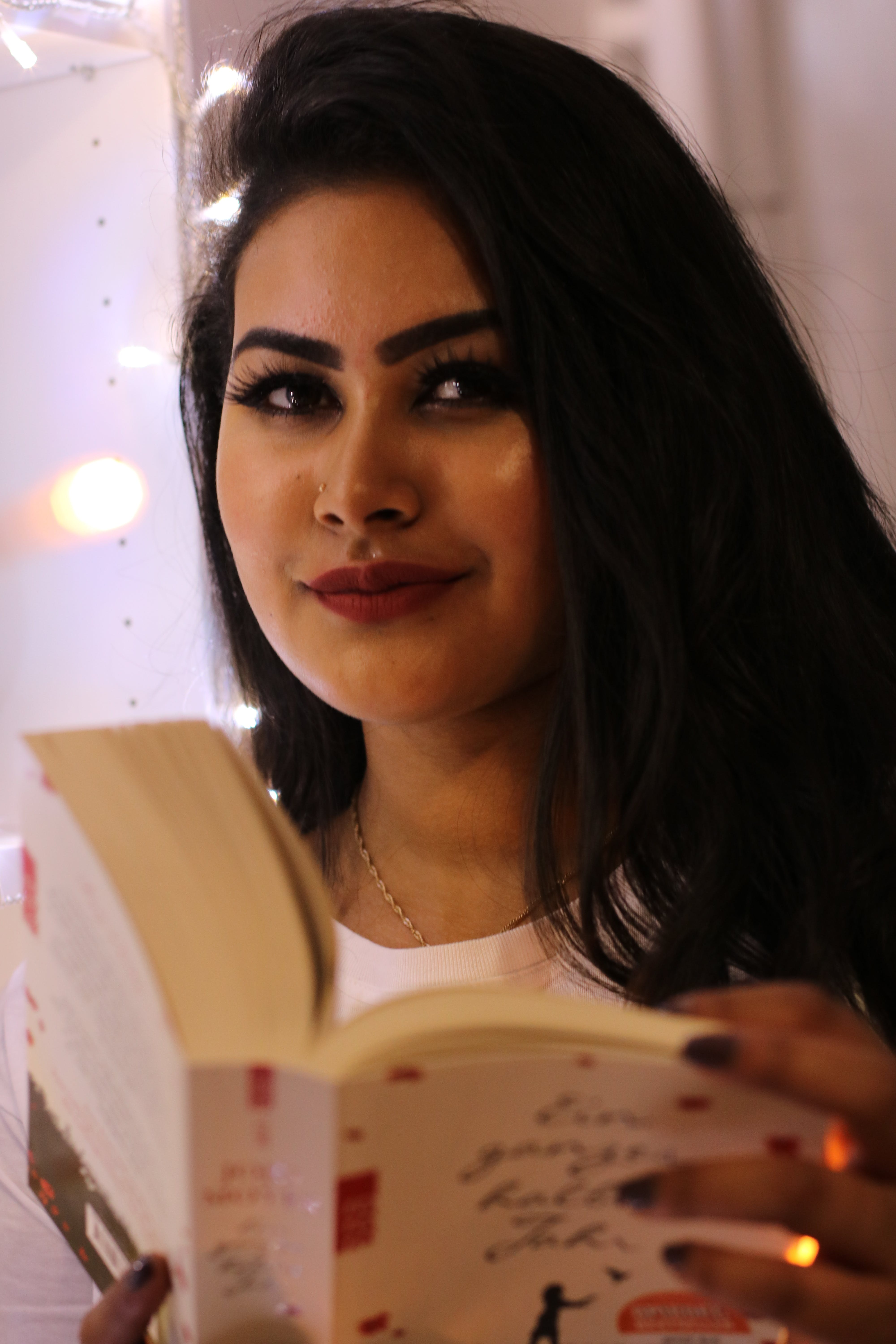 Black Haired Smiling Woman Holding Book
