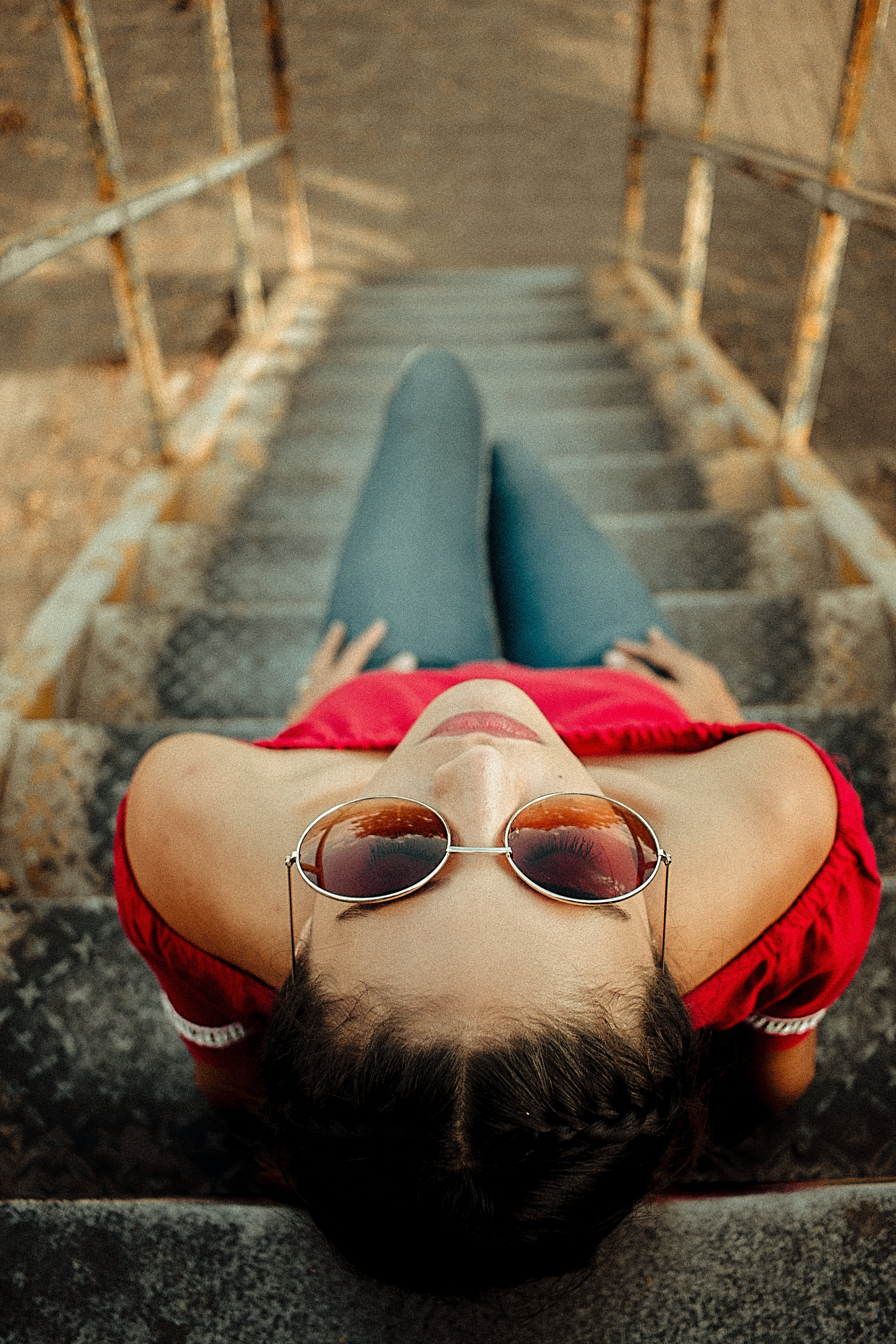 High Angle Photo of Woman Sitting on Metal Staircase