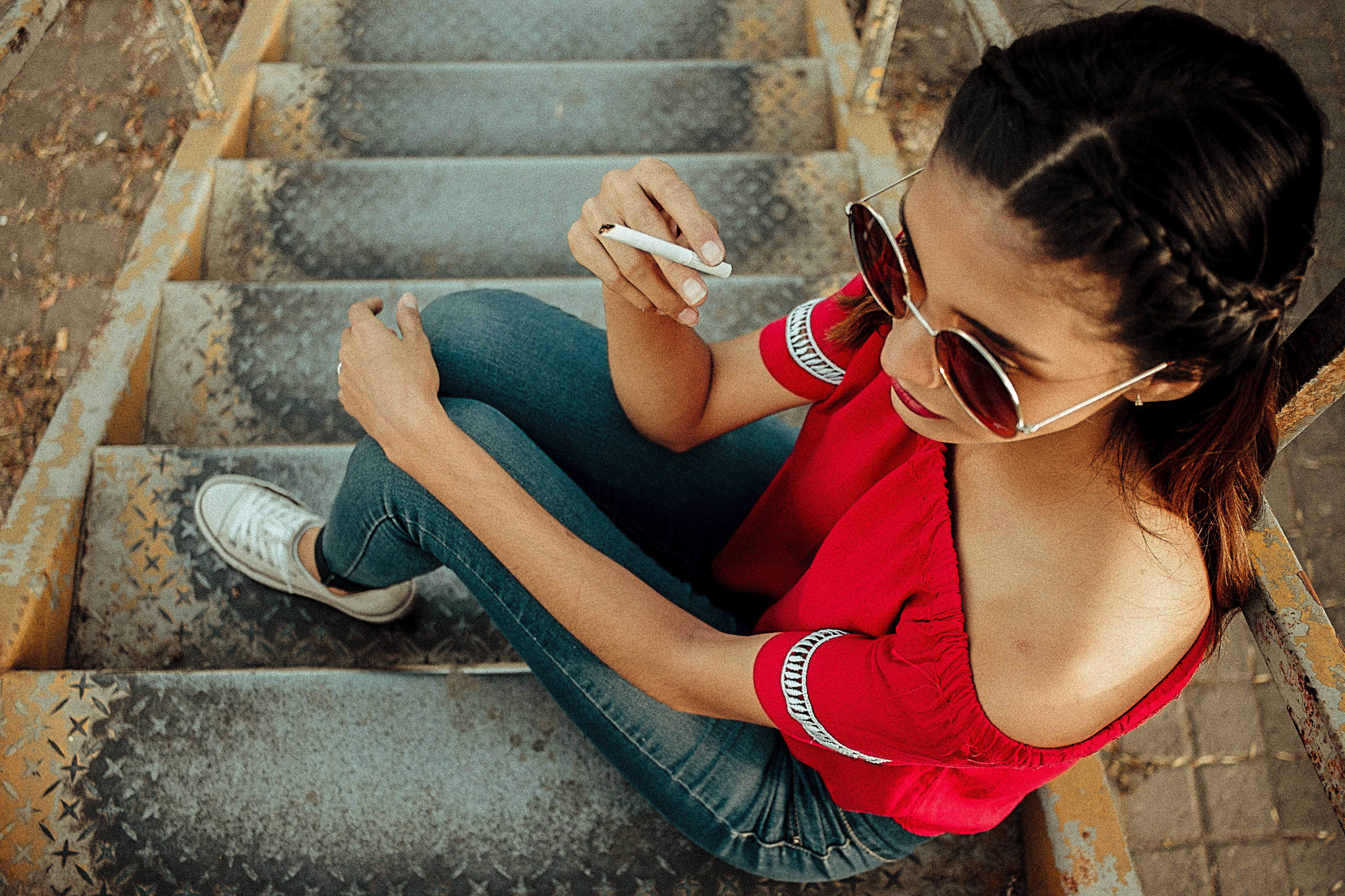 Woman Holding Cigarette Sitting on Stairs