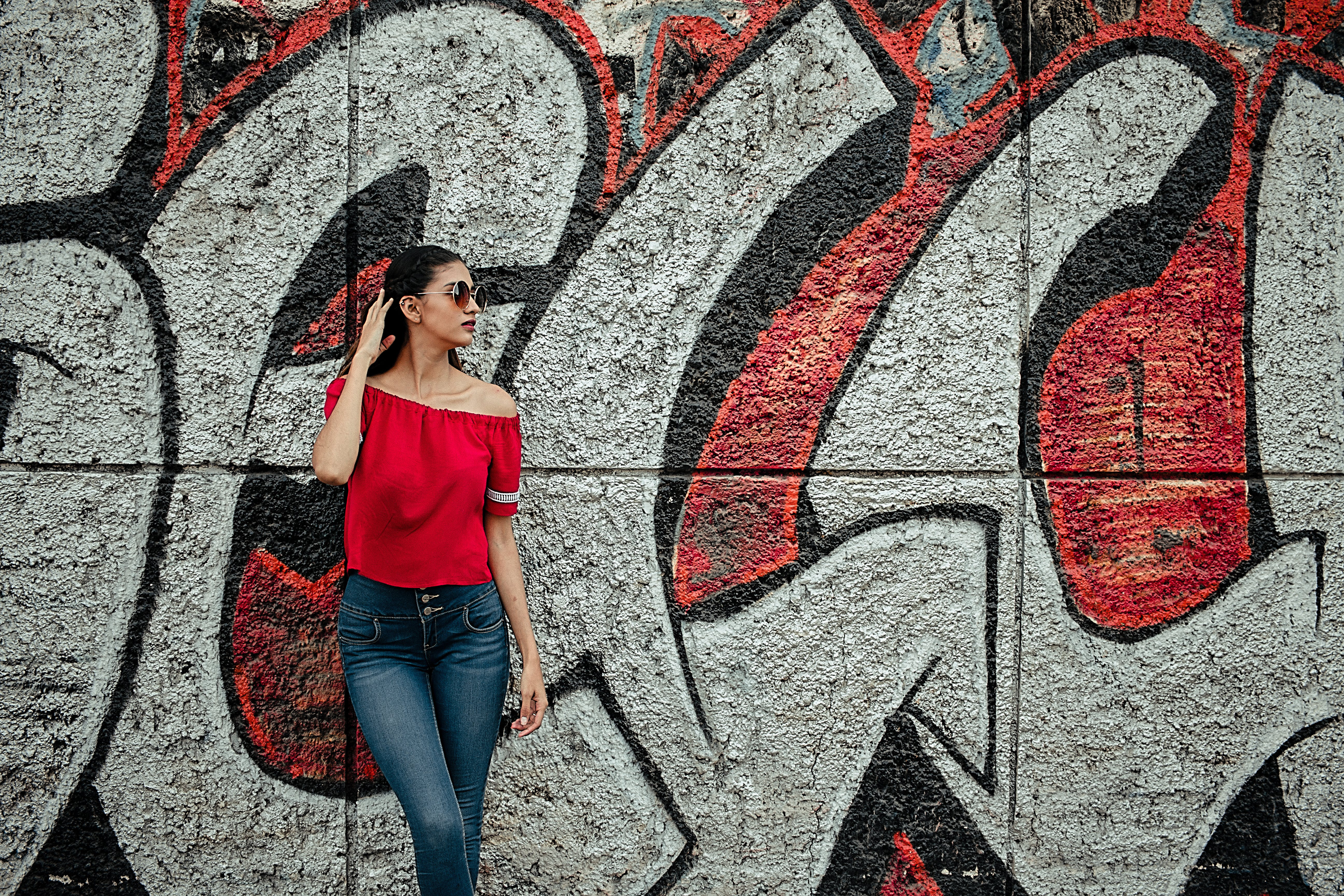 Woman Wearing Red Off-shoulder Shirt and Blue Denim Stone-wash Jeans Near Red and Gray Graffiti Wall