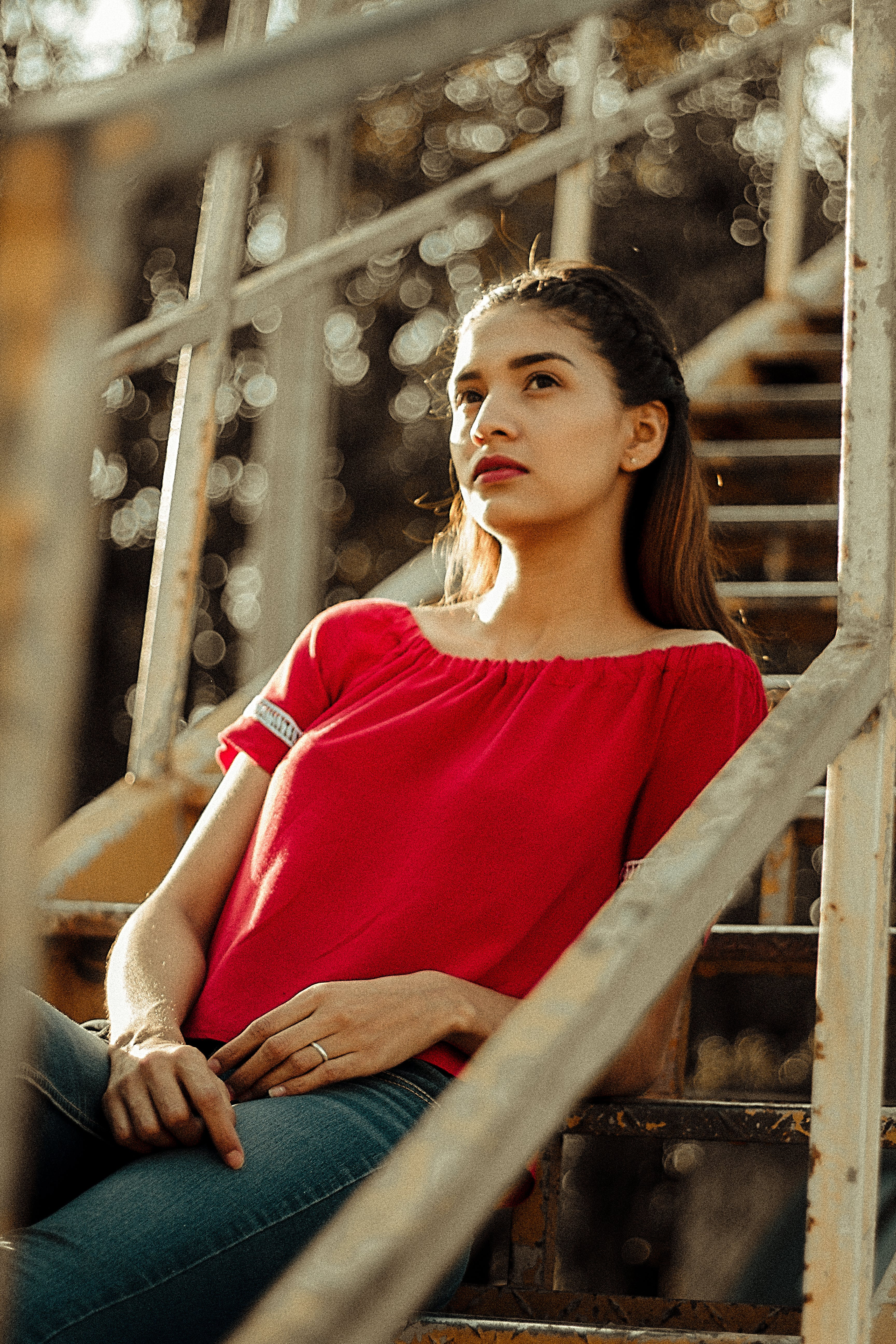 Photo of Woman in Red Blouse Sitting on Metal Staircase