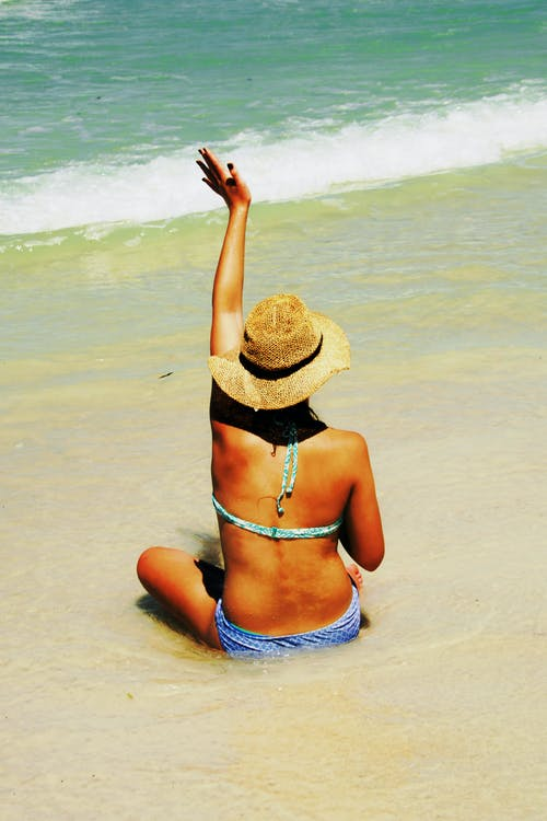 Woman Sitting on Shore Waving Hands