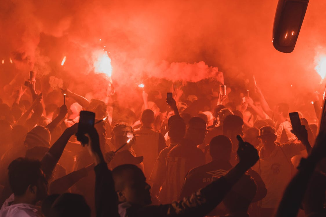 Crowd Holding Flares While Gathered on Open Area at Night Time