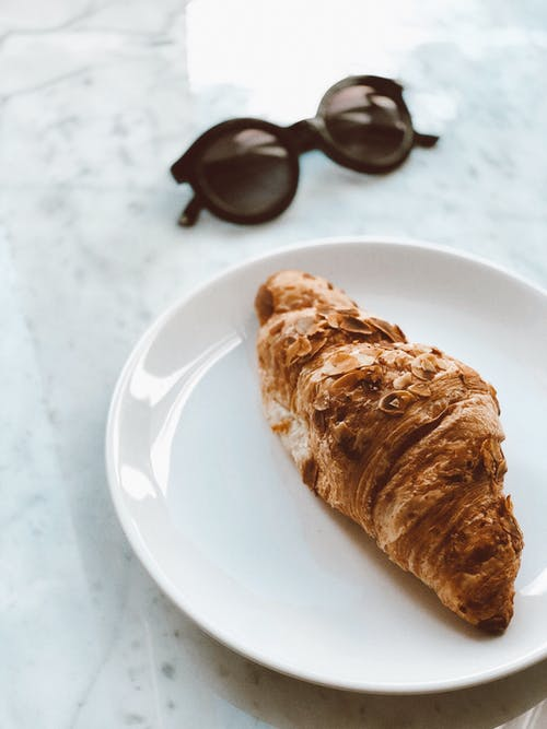 Baked Bread on Plate Beside Black Sunglasses