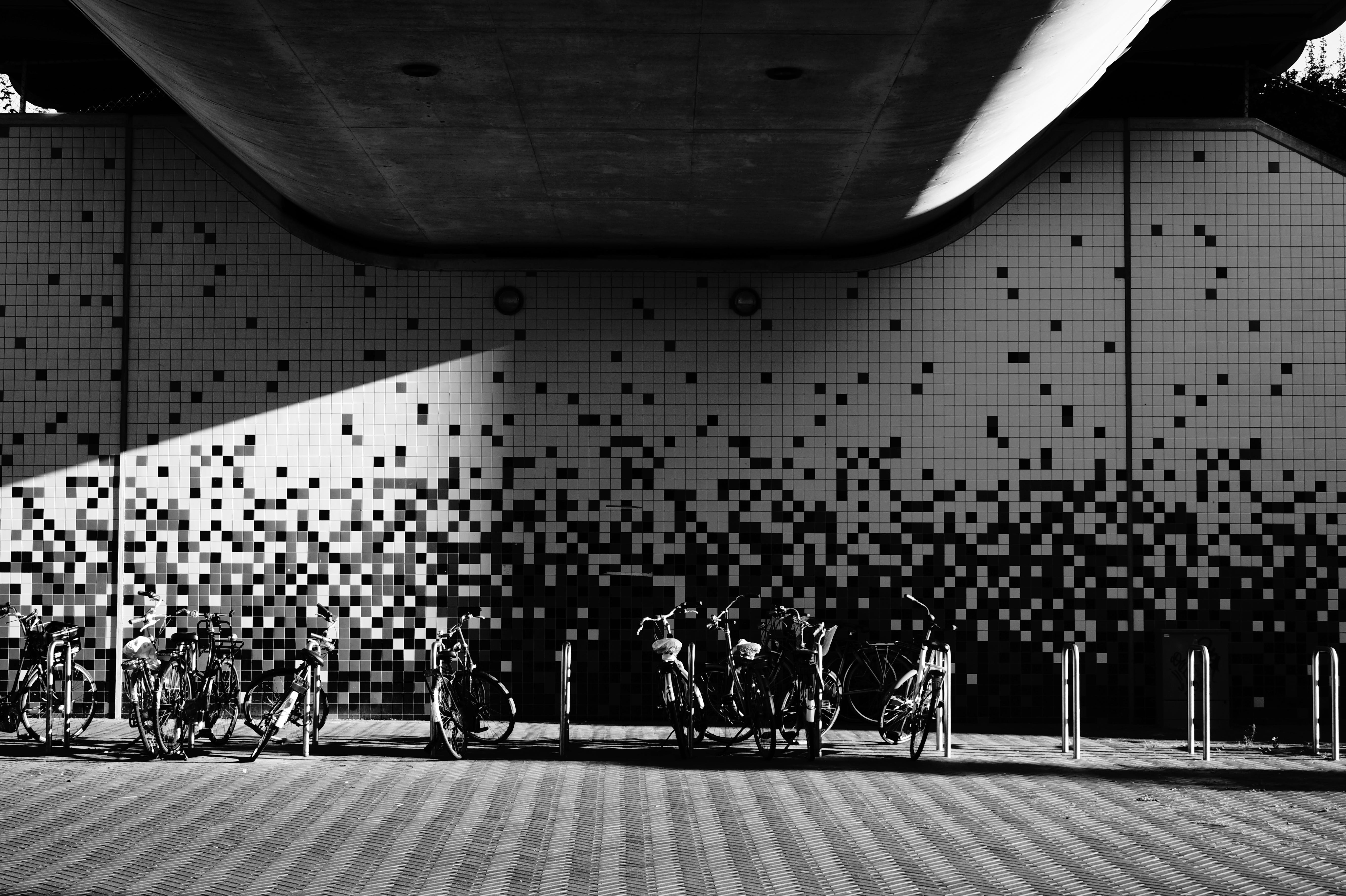 Parked Bikes Under Building in Grayscale Photography