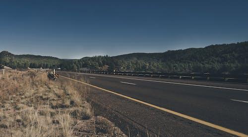 Kostnadsfri bild av asfalt, bergen, dagsljus, gräs