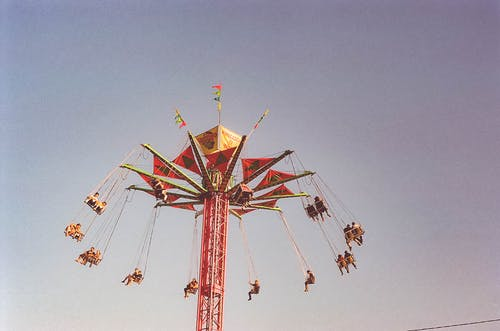 People Riding on Amusement Ride Taken Under Clear Sky