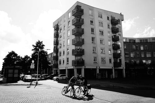 Grayscale Photo of Two Men Riding Bike Beside Building