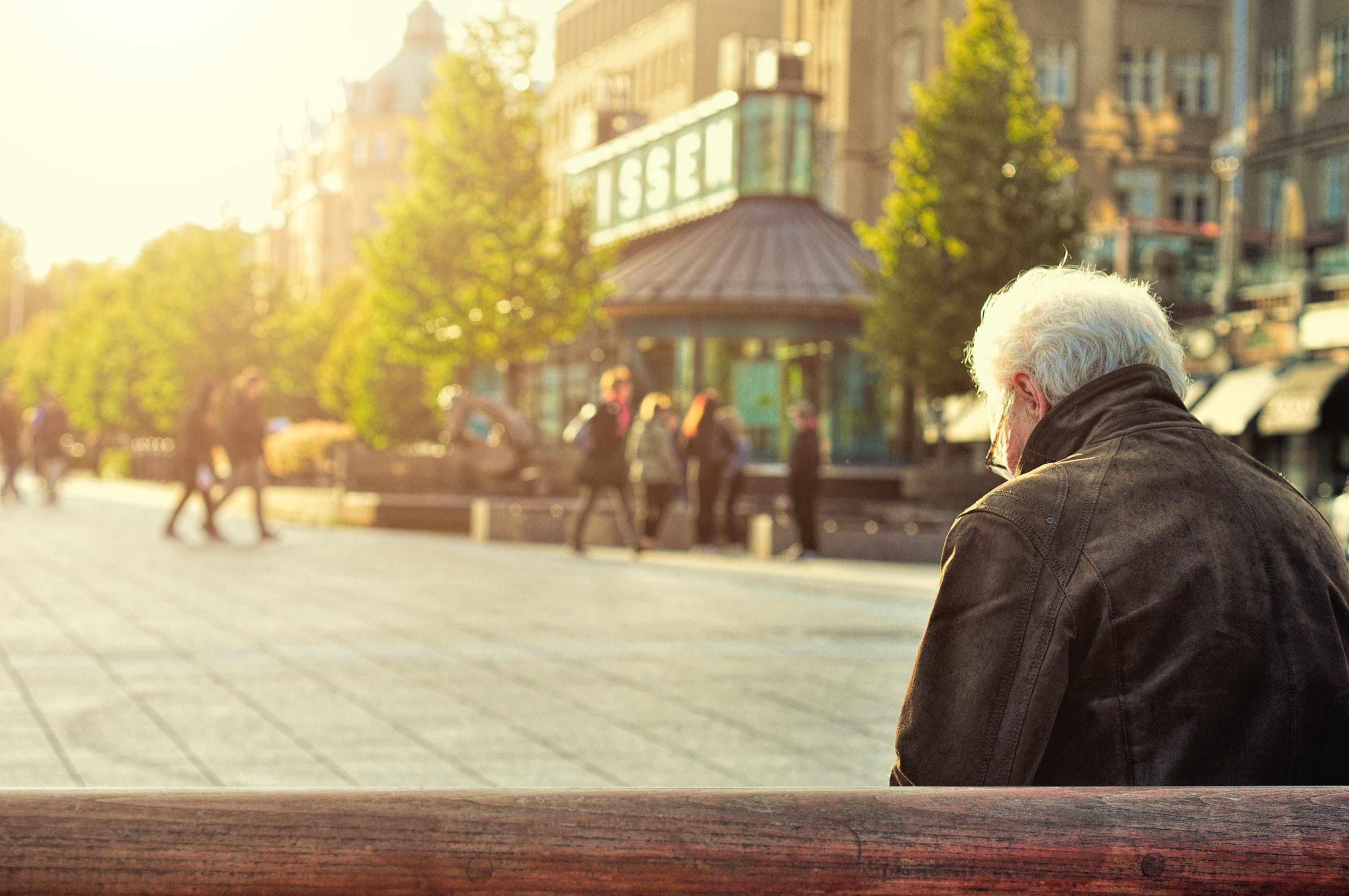 Man Sitting on Wooden Bench Wearing Black Leather Jacket