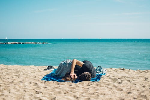 Man and Woman Lying on Blue Textile at Seashore