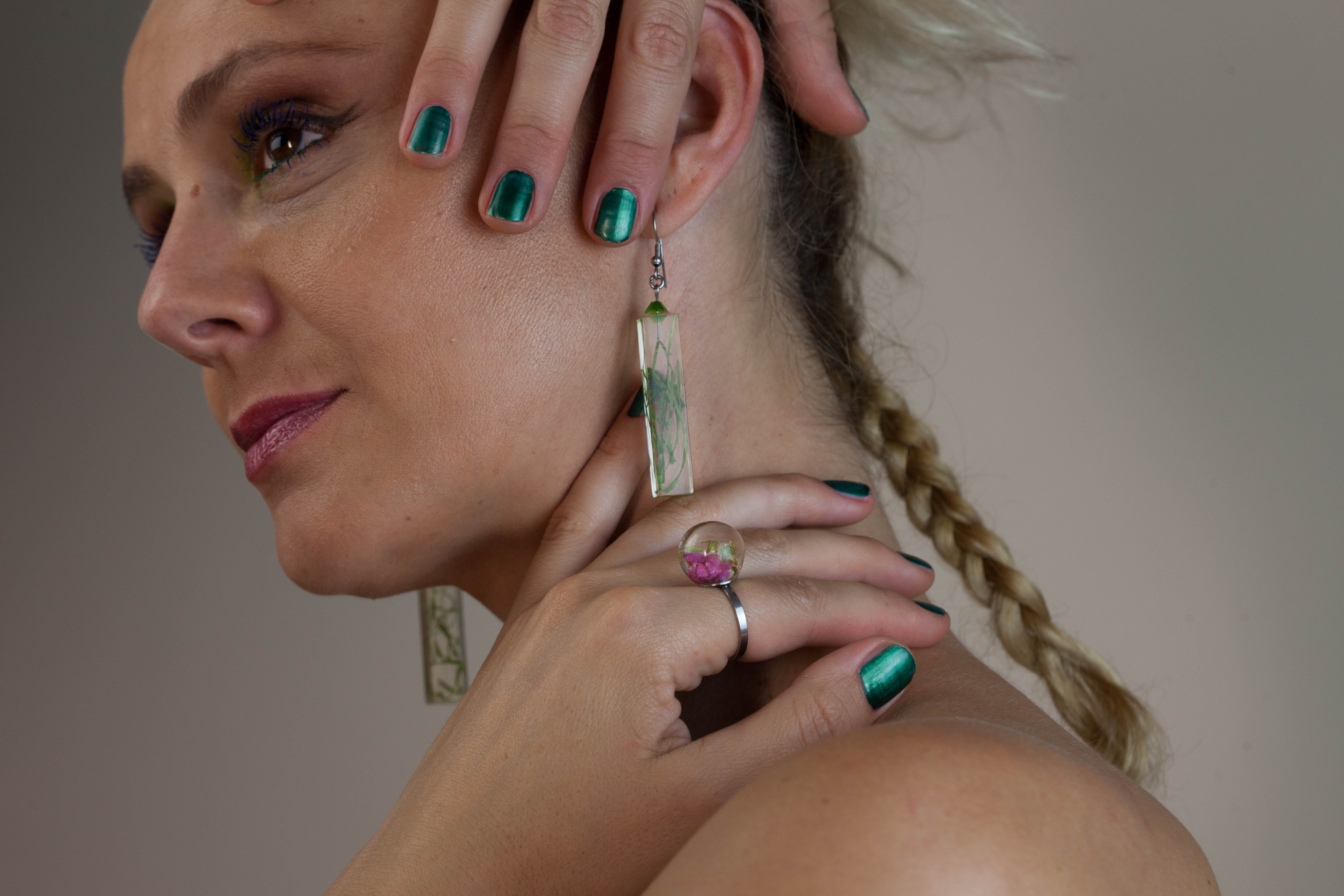 Woman Wearing Earrings While Holding Her Neck