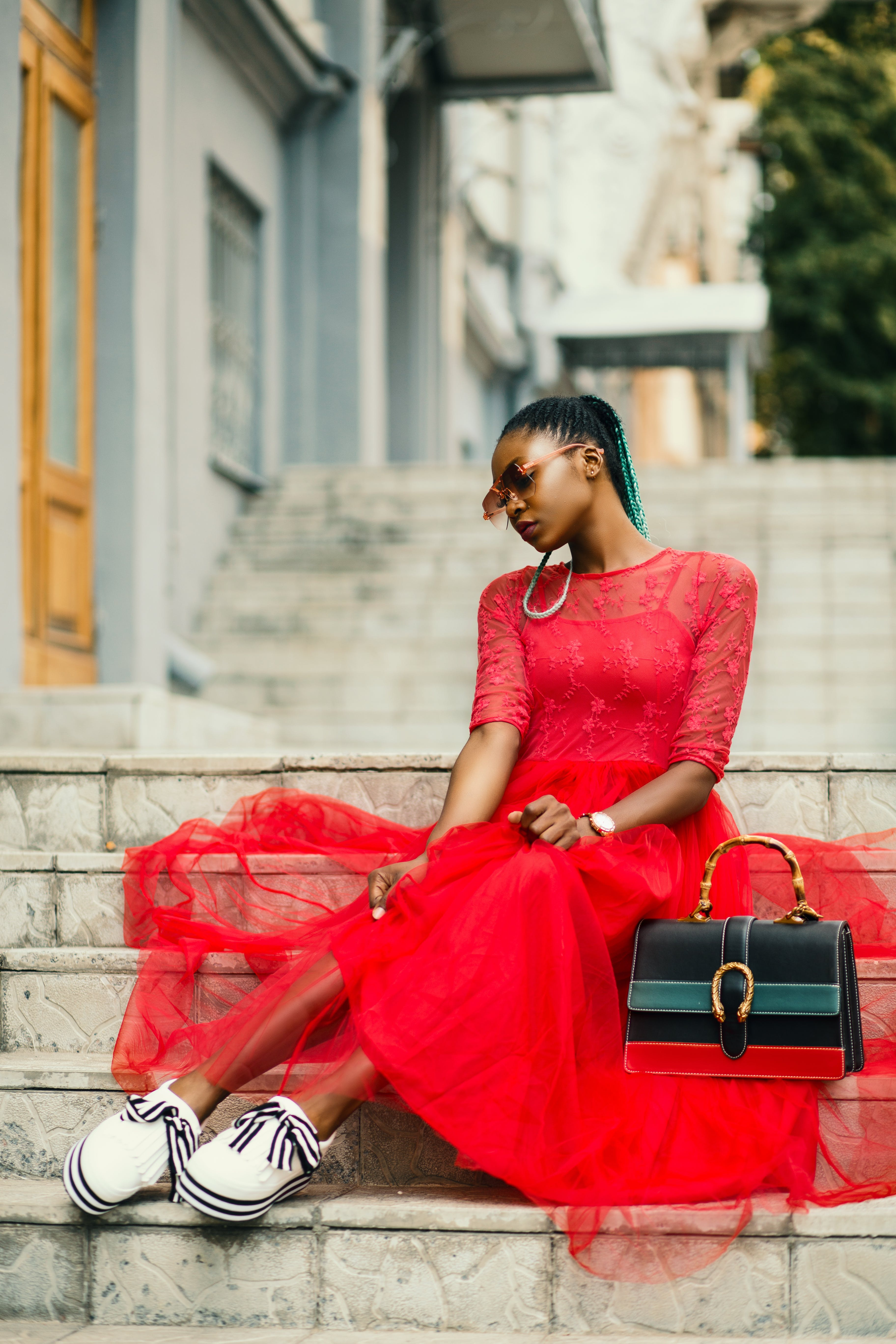 Woman Wearing Red Long-sleeved Dress Near Black Leather Bag Sitting on Concrete Stairs Posing for Photoshoot