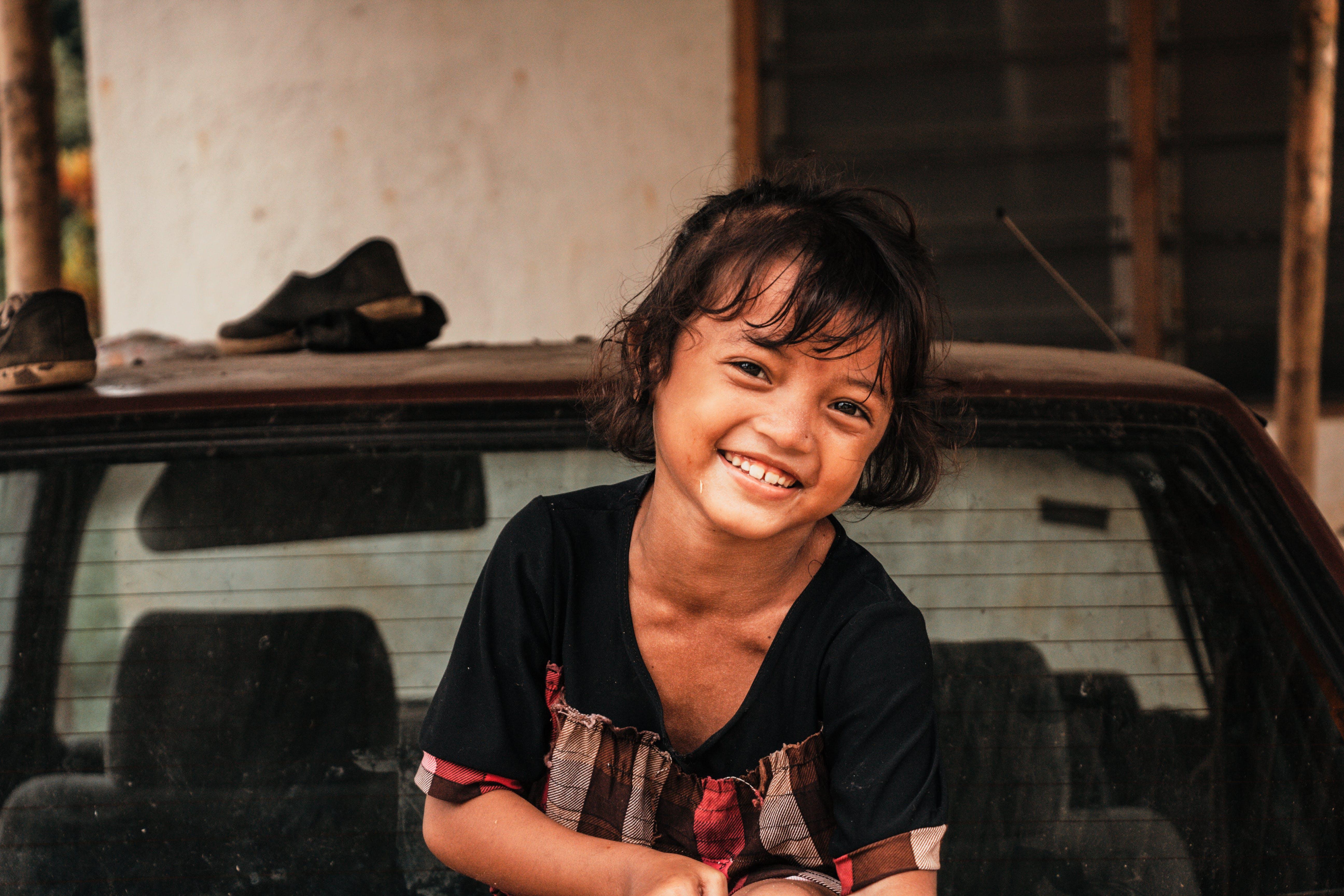 Smiling Girl Sitting Top of Vehicle