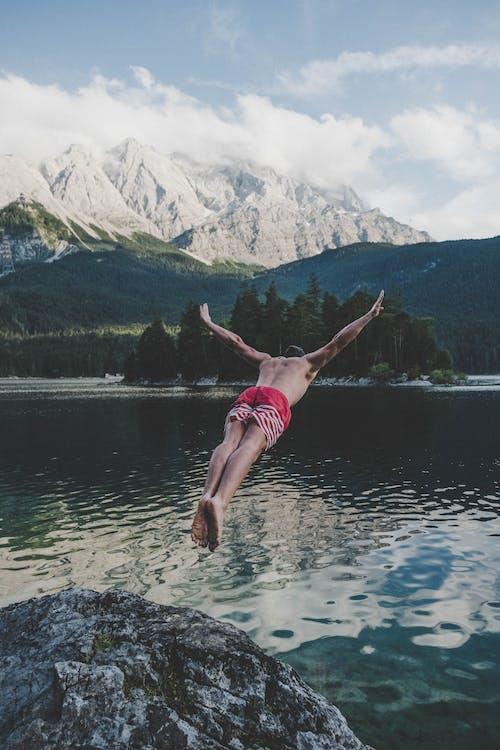 Homem Vestindo Shorts Listrados De Vermelho E Branco, Mergulhando Em Brown Rock