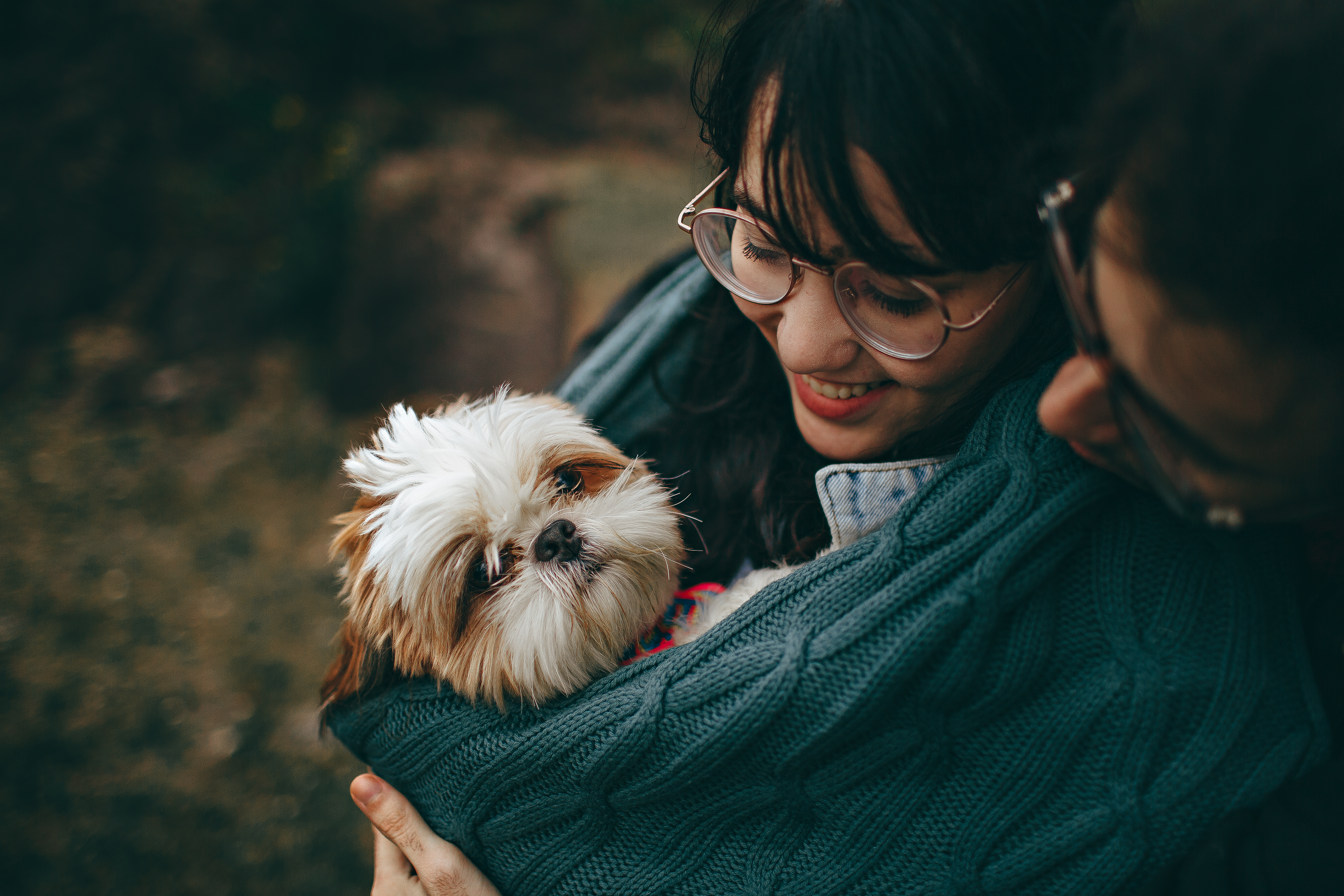 Selective Focus Photography of White and Tan Shih Tzu Puppy Carrying by Smiling Woman