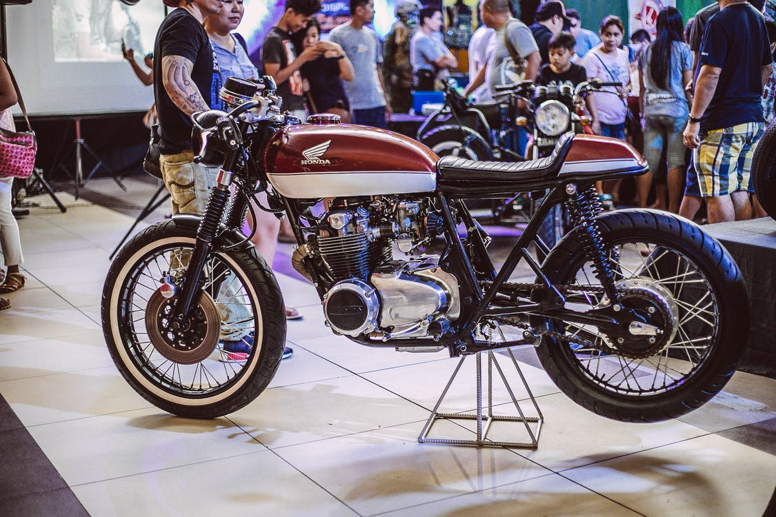 Brown Honda Motorcycle Displayed Inside Building With People