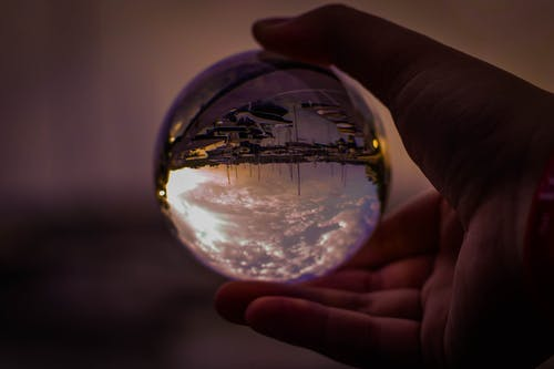 Selective Focus Photography of Person Holding Glass Ball