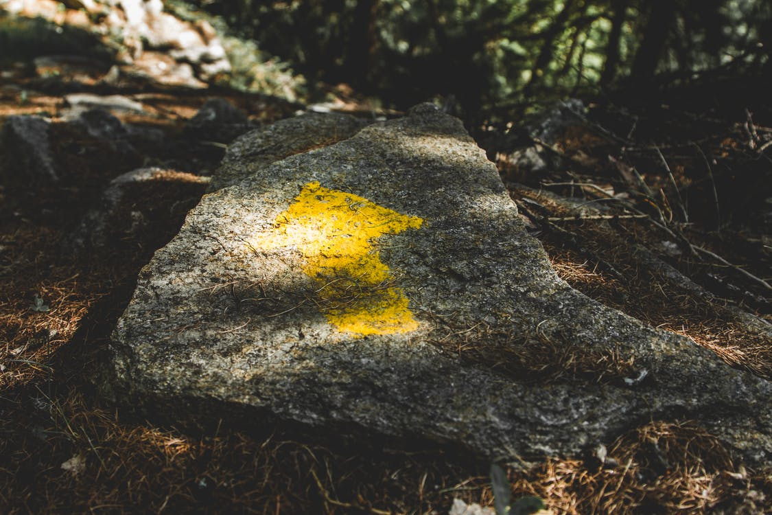 Yellow Arrow Painted on Gray Stone