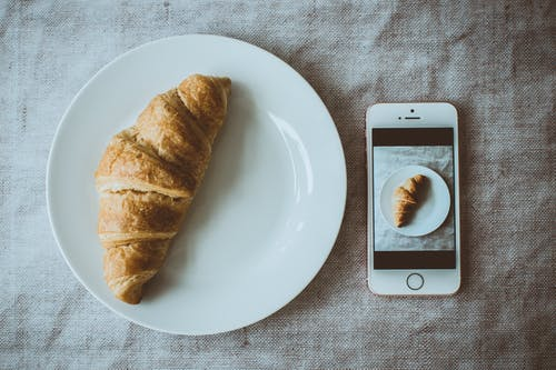 Croissant Bread on Round White Plate Beside Rose Gold Iphone Se Displaying Photo of Croissant Bread on Plate