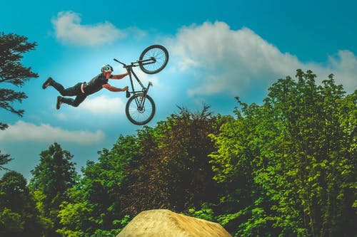 Man Holding Bike Up In The Air Under Blue Sky