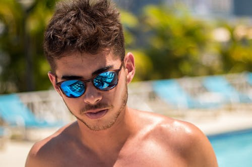 Topless Man Wearing Blue Lens Sunglasses