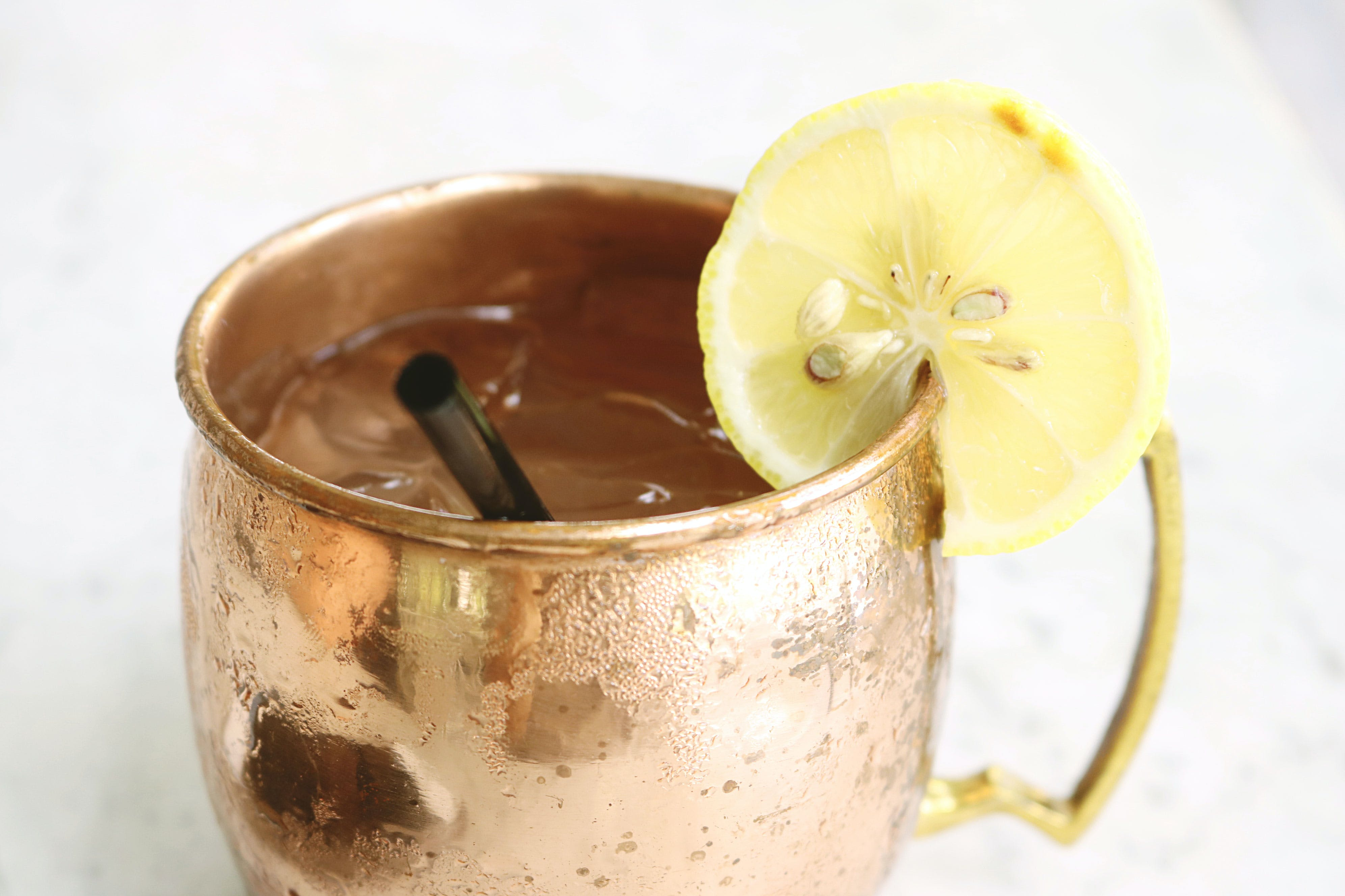 Brass Mug Filled With Clear Liquid and Slice of Lemon