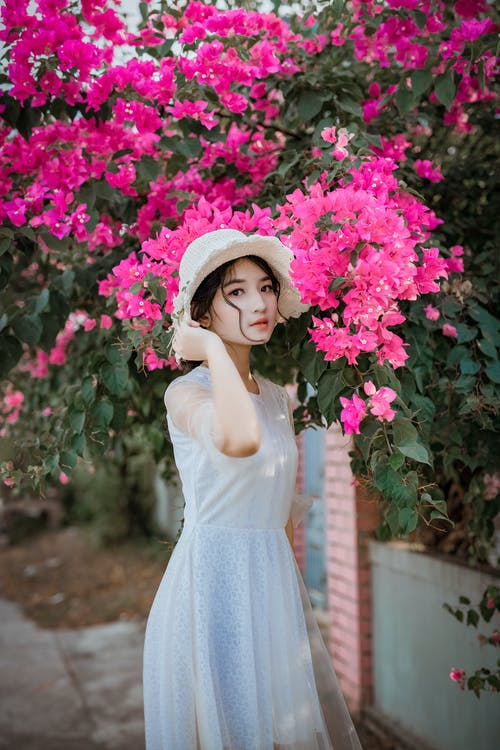 Woman Holding Her Hat While Standing In Front Of Pink Bougainvillea Flowers