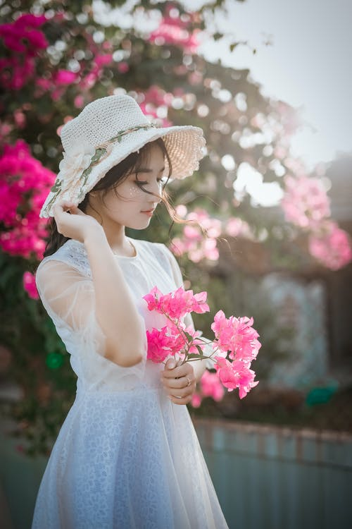 dc48e6ad367 Woman Wearing Sun Hat and White Dress Holding Pink Bougainvilleas