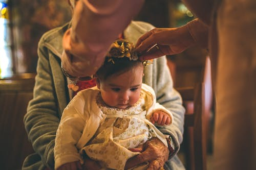 Person Putting Crown On Baby