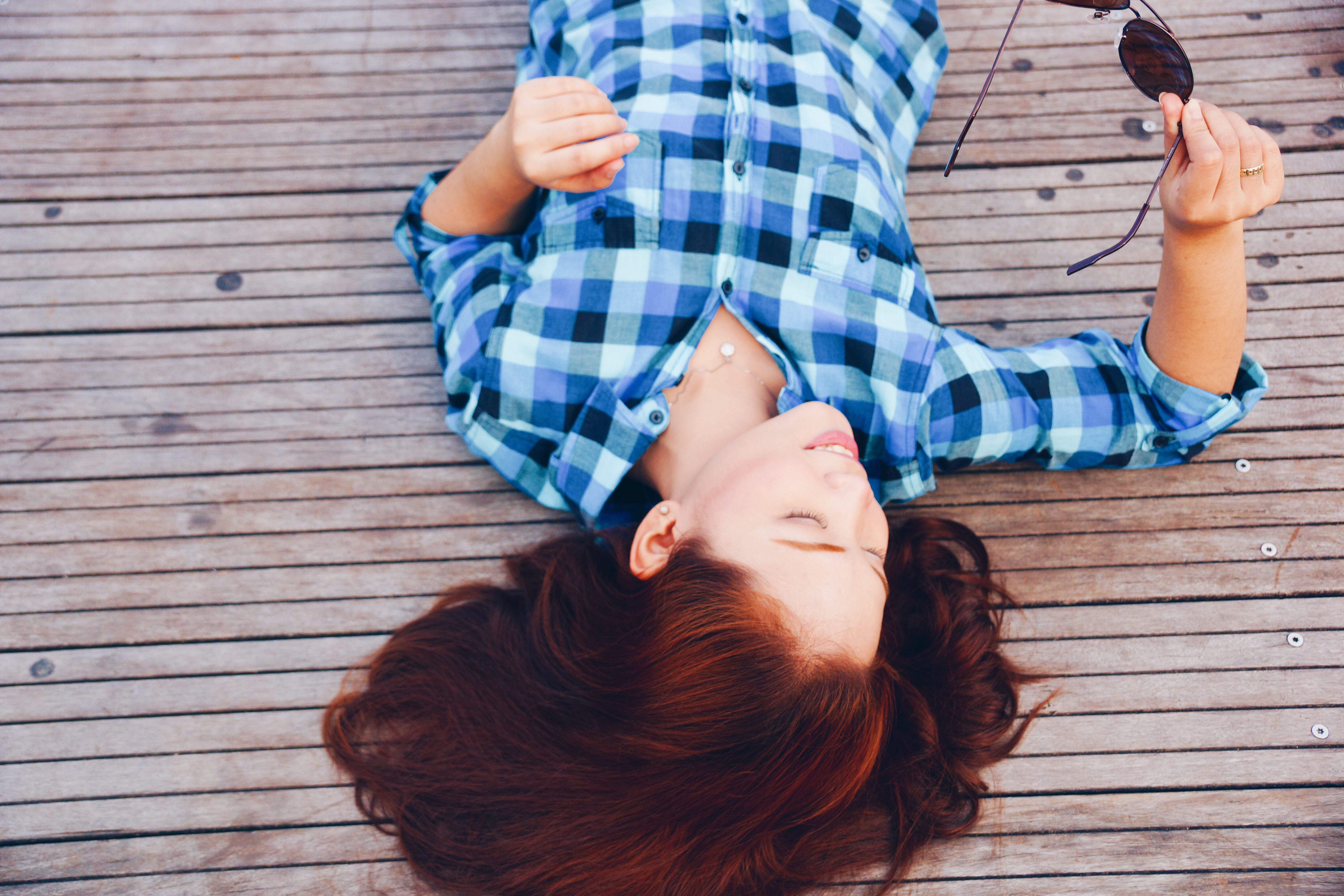 Woman Lying on Wooden Surface Holding Sunglasses