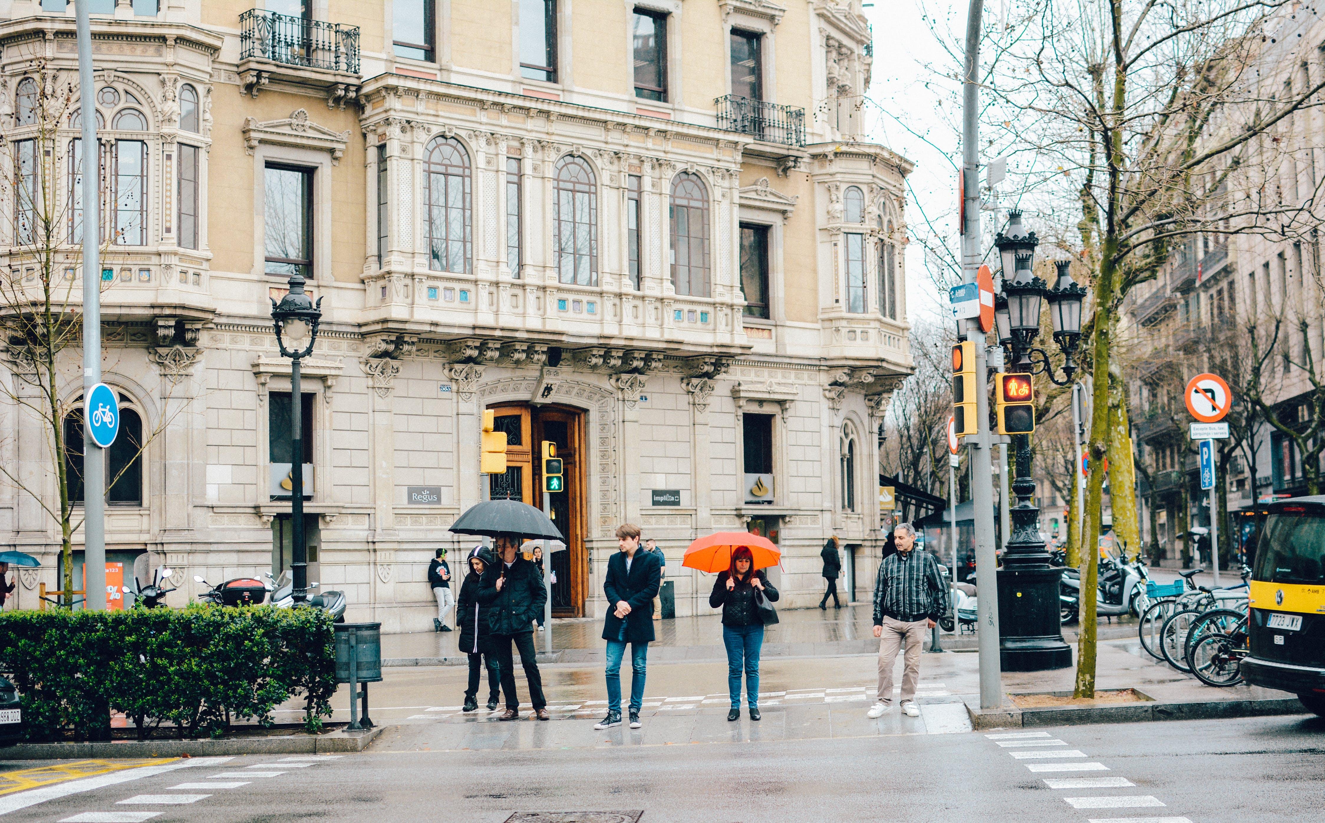 Group of People Walking Beside Beige Building