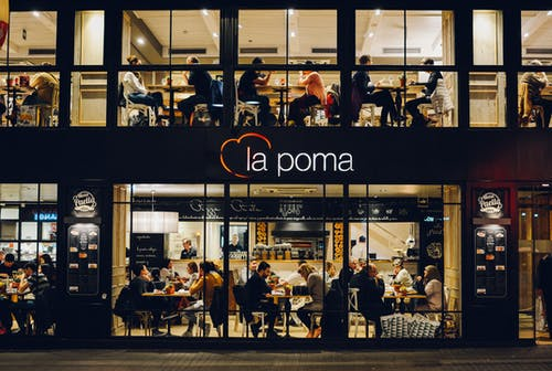 People at La Poma Store Front at Night
