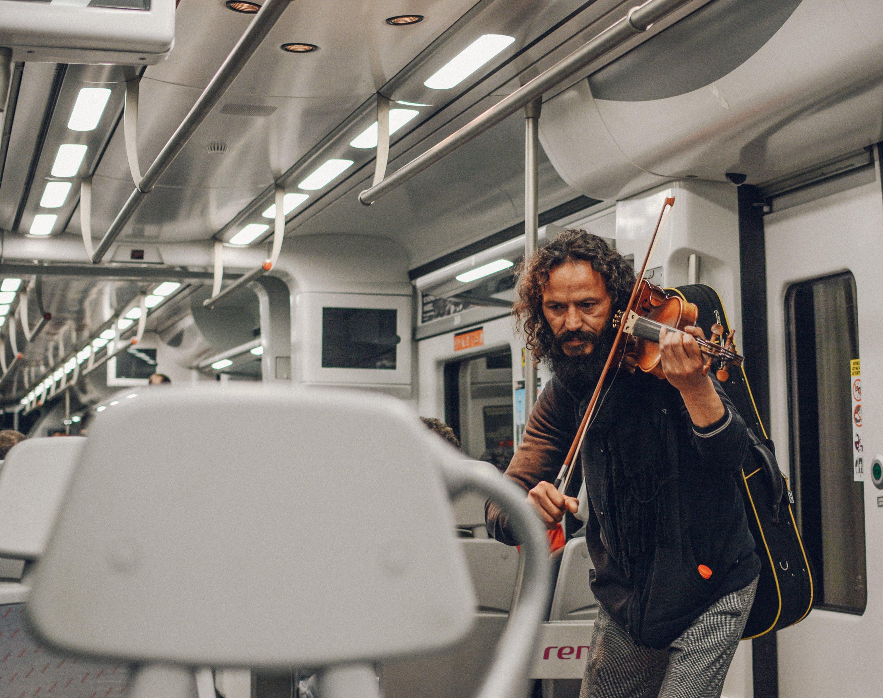 Man Playing Violin Inside Train