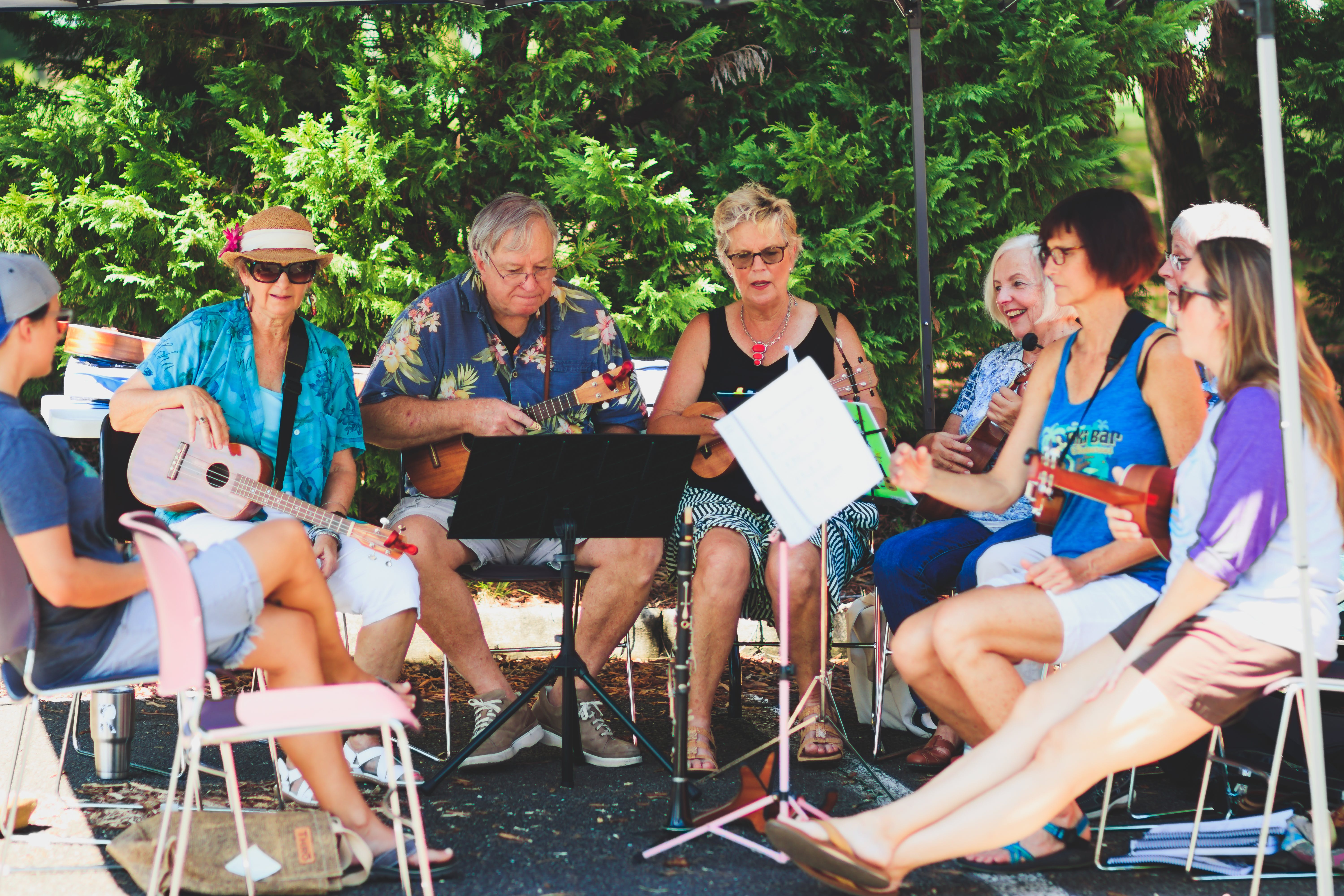 Group of People Sitting Down Playing Music Instruments